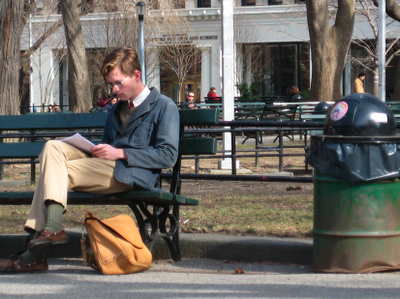 :nice studious boy reading a rectangular book on a rectangular bench: